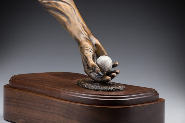 close up view of bronze golf sculpture hand holding golf ball cremation urn funeral memorial