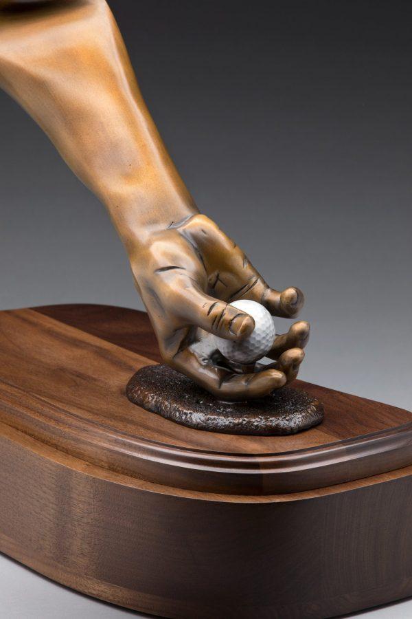 Closeup of bronze golf cremation urn memorial hand holding golf ball